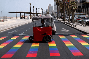 People ride over a rainbow-colored pedestrian crossing before the gay pride parade in Tel Aviv on June 3, 2016. BAZ RATNER/REUTERS